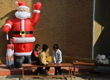 Indian children play next to an inflated figure of Santa after attending Christmas mass at 'Our Lady of Vailankanni' Church, in Bengaluru.