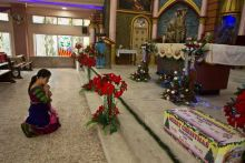 A woman offers prayers on Christmas day at a Church in Guwahati