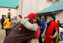 Indian's hug each other as they celebrate Christmas outside the holy family Catholic Church, in Srinagar
