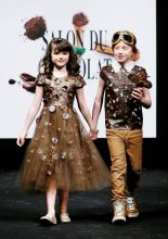 Two children walk down the ramp in outfits made of chocolate. Both of them had truffles and leaves on their clothes. And the highlight of this picture--notice the airplane the boy is holding? Pure dark chocolate!