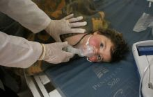 Syrian doctor treats a child in makeshift hospital