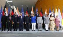 Angela Merkel and Narendra Modi pose with members of their delegations for a family photo ahead of the 4th round of German-Indian government consultation at the German Chancellery.