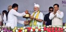 PM Modi being presented a memento at the public address in Assam's Dhola.
