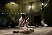 A Muslim American man holds up his hands in prayer after breaking fast and performing the Maghrib sunset prayer at the Islamic Cultural Center in Manhattan, New York, US.