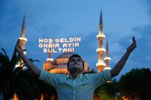 Backdropped by the iconic Sultan Ahmed Mosque, better known as the Blue Mosque, a man poses for a picture in the historic Sultanahmet district of Istanbul during the fasting month of Ramzan. The lights read in Turkish: 'Welcome, the Sultan of 11 months'.