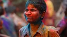 A visually impaired student smeared with coloured powder plays holi at a school in Mumbai