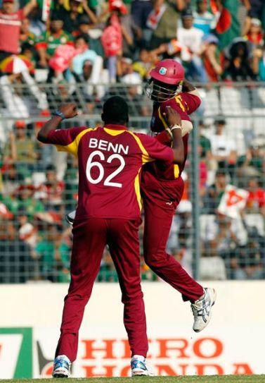 West Indies left-arm spinner Sulieman Benn celebrates the wicket of Shafiul Islam with captain Darren Sammy