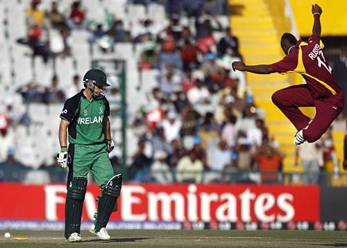 Ireland batsman Ed Joyce walks away after being bowled out by West Indies paceman Andre Russell