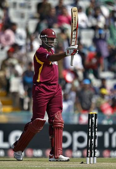 West Indies batsman Kieron Pollard raises his bat after scoring his half-century
