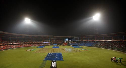 Plastic sheets cover the pitch area at the M Chinnaswamy Stadium