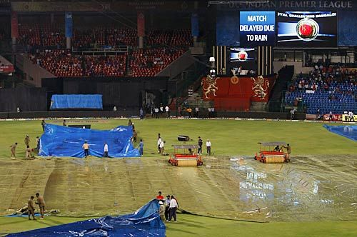 Groundskeepers keep the pitch area dry