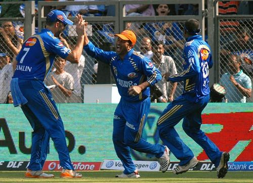 Mumbai captain Sachin Tendulkar and team-mates celebrate the wicket of Pune openers Jesse Ryder