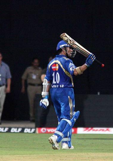 Mumbai captain Sachin Tendulkar raises his bat post his century