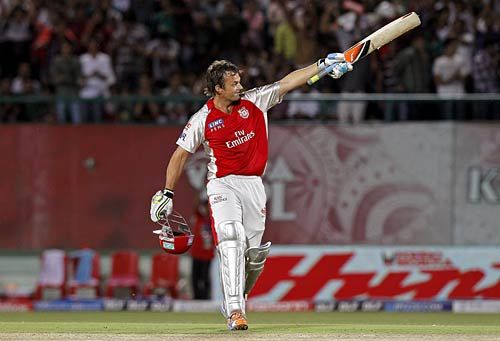 Punjab captain Adam Gilchrist raises his bat after a century