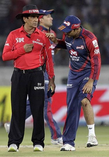 Delhi captain Virender Sehwag shows his injury to umpire Asad Rauf