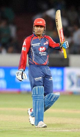 Delhi captain Virender Sehwag raises his bat to mark his first T20 century