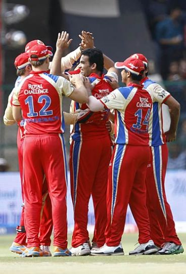 Bangalore paceman Zaheer Khan (centre) celebrates the wicket of Chennai opener Michael Hussey with team-mates