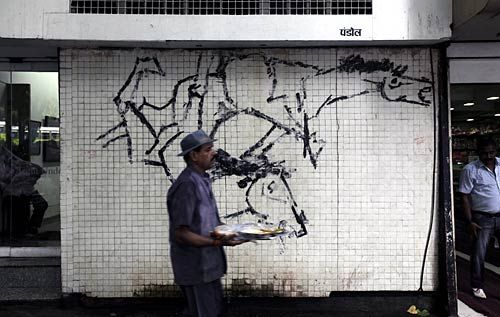 Man walks by a Husain painting