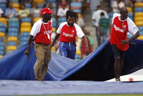 Grounds workers bring out the covers as rain stopped play