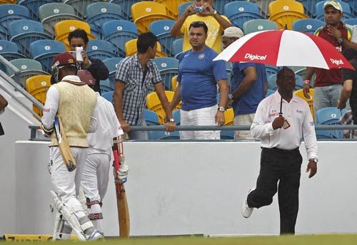 West Indies batsmen Marlon Samuels (left) and Shivnarine Chanderpaul walk off