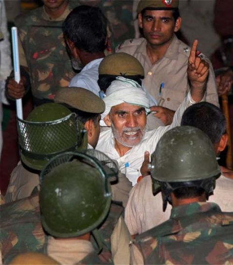 Policemen evict a supporter of Baba Ramdev from Ramlila Ground in New Delhi
