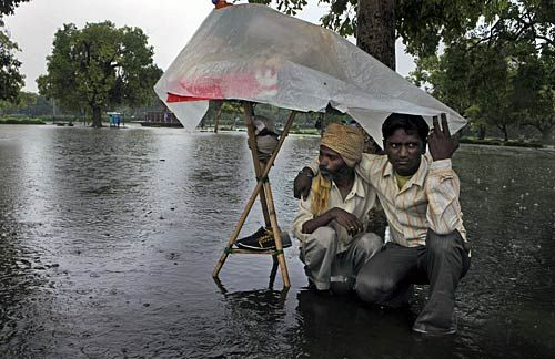 Street vendors at India Gate use a plastic sheet to cover themselves from rain