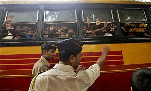 Schoolchildren wave out from inside a bus as they drive past policemen at the site of a blast site at Dadar