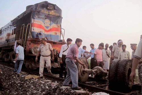 Villagers and policemen look at the wreckage after a running train hit a bus in Uttar Pradesh.