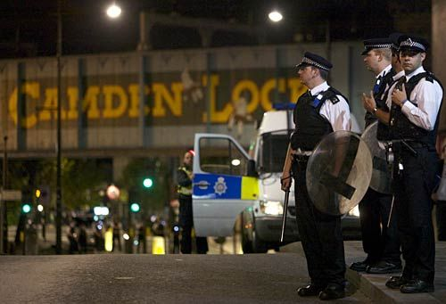 British police officers stand guard on a street following skirmishes with police in Camden Town, north London