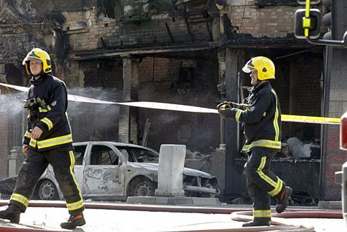 Firefighters prepare the area in front of a burnt building in Croydon, south London