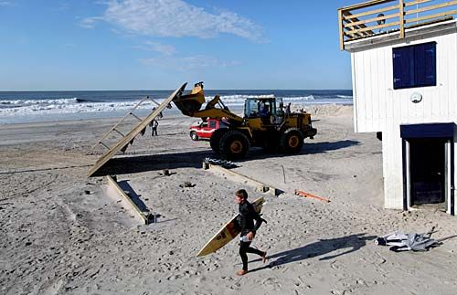 Cleanup continues as a surfer passes a dislodged lifeguard shack in Long Beach, N.Y.