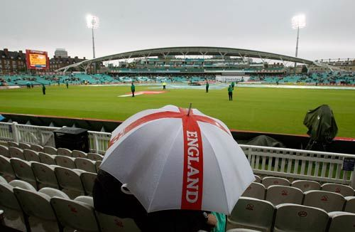 A couple shelter take shelter from the rain at The Oval