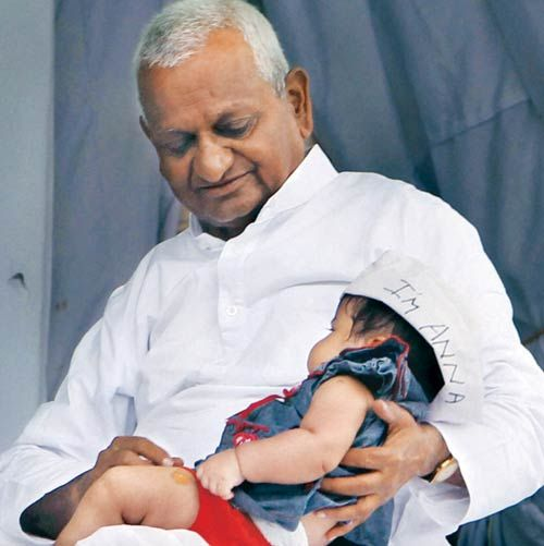 Anna Hazare holds a child in New Delhi on Day 6 of his fast.