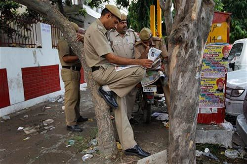Policemen posted outside Tihar prison read newspapers