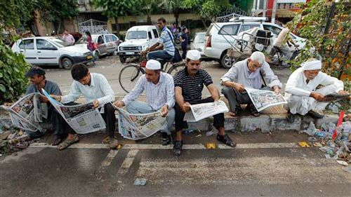 Supporters of Anna Hazare read newspapers outside Tihar prison
