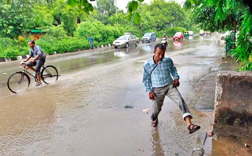 A man wades through a flooded street in Delhi