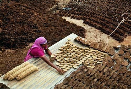 Woman collects earthen lamps