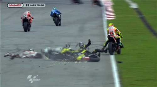 Marco Simoncelli slides across the track after collission