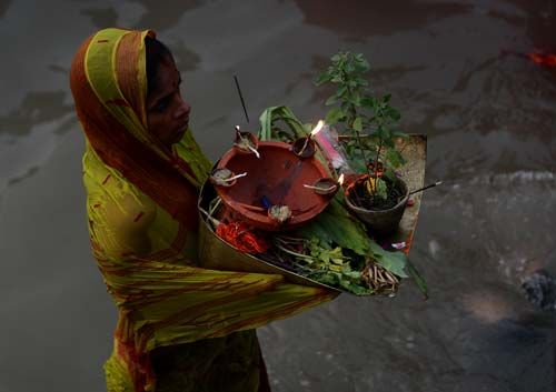 A devotee offer prayers during Chhath puja