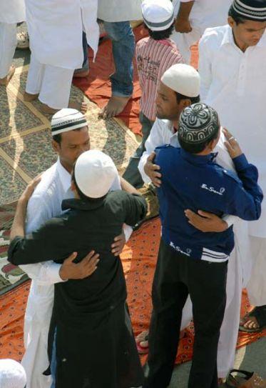 People hug each other on Eid