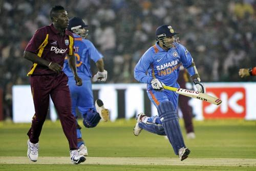 Virender Sehwag (right), Virat Kohli and as West Indies bowler Andre Russell
