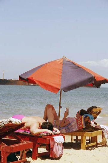 Tourists sunbathe at Goa beach