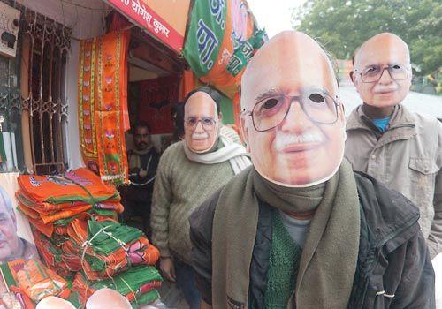Men wearing masks of top BJP leaders