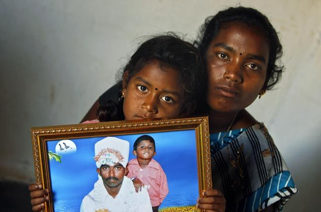 Shwetha with her mother Sunita holds a photograph of her father Hari Prasad