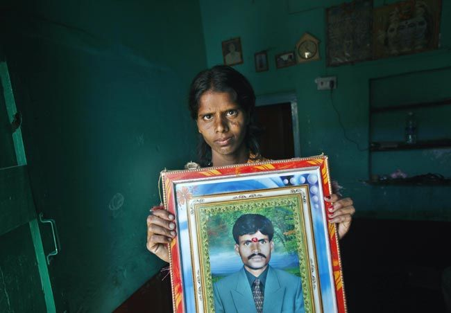 Ramanjamma holds a picture of her debt-ridden husband