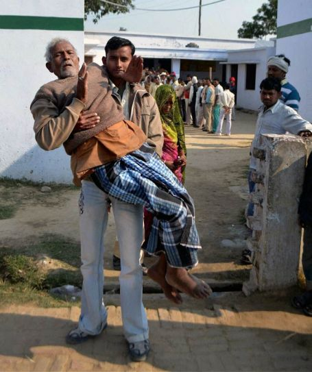 A paralyzed voter is carried by a relative