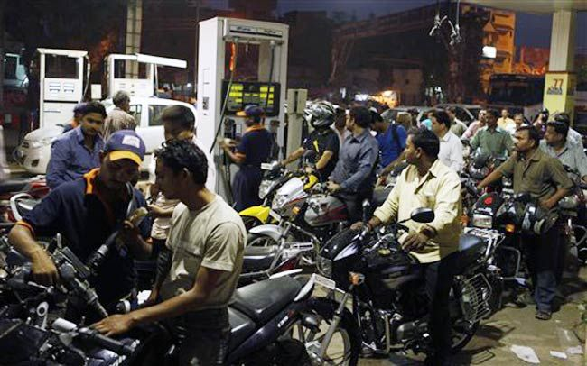 Motorists crowd a fuel pump