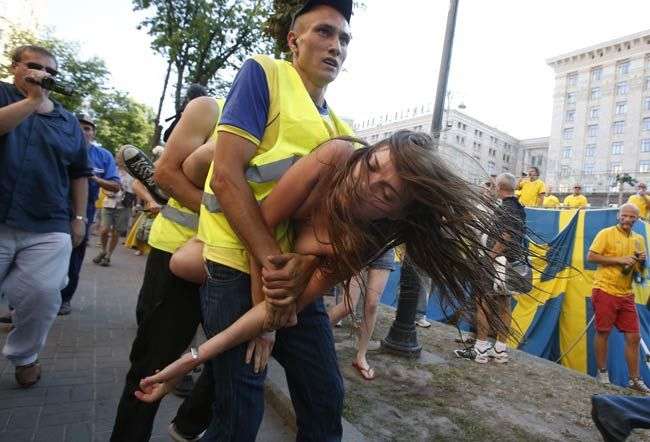 A protester from Ukrainian women rights group Femen is carried away by security guards.