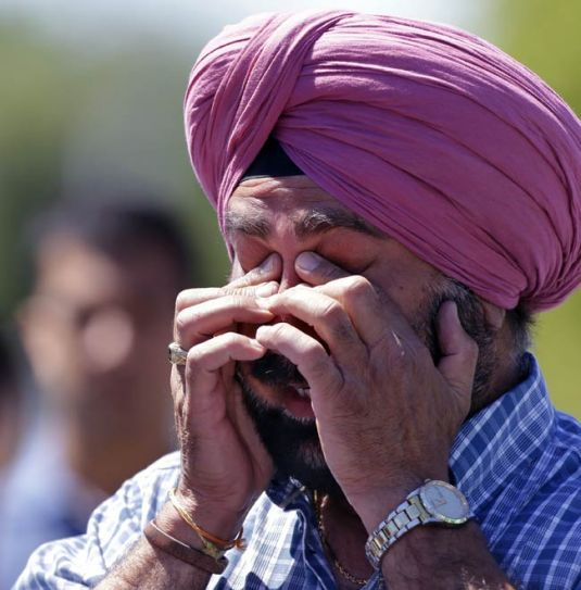 A man reacts outside the Gurdwara in US