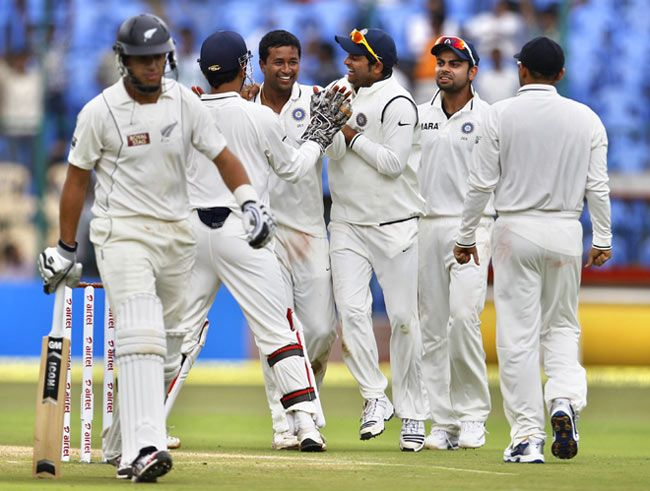 Pragyan Ojha (centre without cap), his team-mates and Ross Taylor